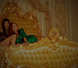 Two gorgeous woman in bedroom Versailles and Baroque vintage style, ladies laying at beautiful and luxurious interior. Concept of rest and relax in luxury hotel